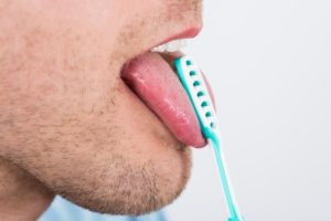 55666928 - close-up of young man cleaning his tongue with scraper